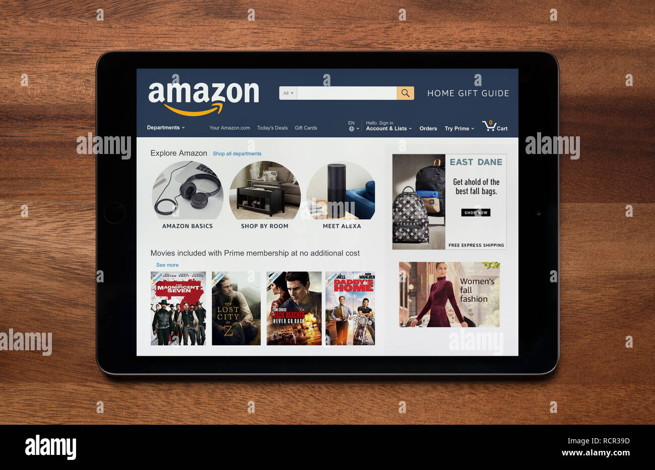 The website of Amazon is seen on an iPad tablet, which is resting on a wooden table (Editorial use only). - Stock Image