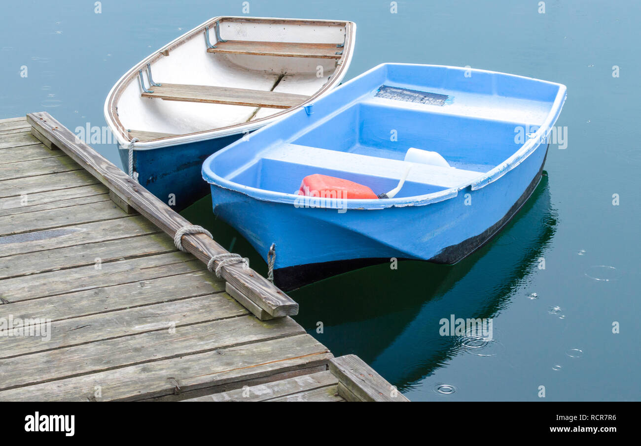 two small rowboats tied to a weathered wooden pier with raindrops hitting the water - Stock Image
