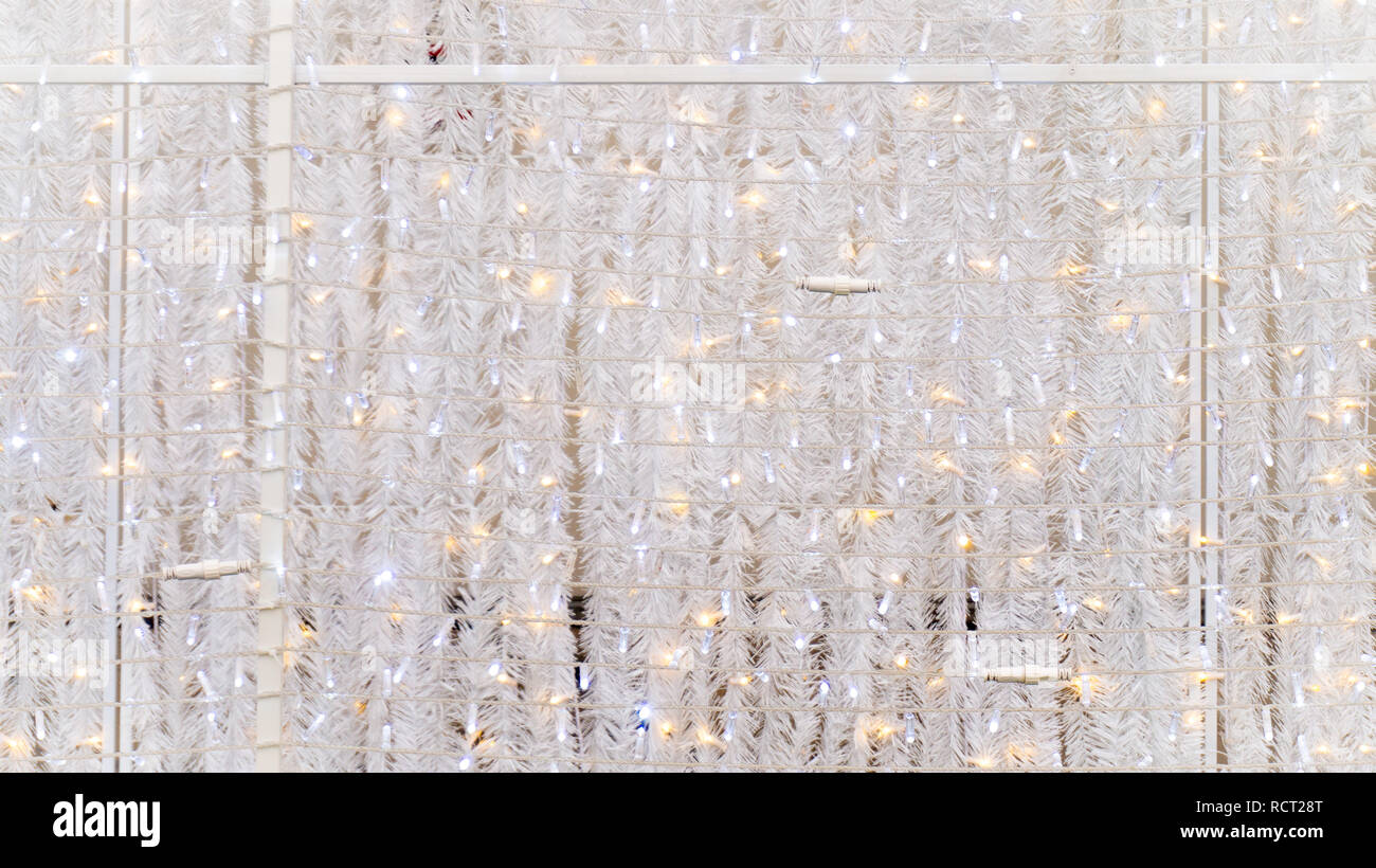 White shimmering Christmas garlands and string lights as a wall covering, used as event decoration. usable for a background graphic resource. - Stock Image