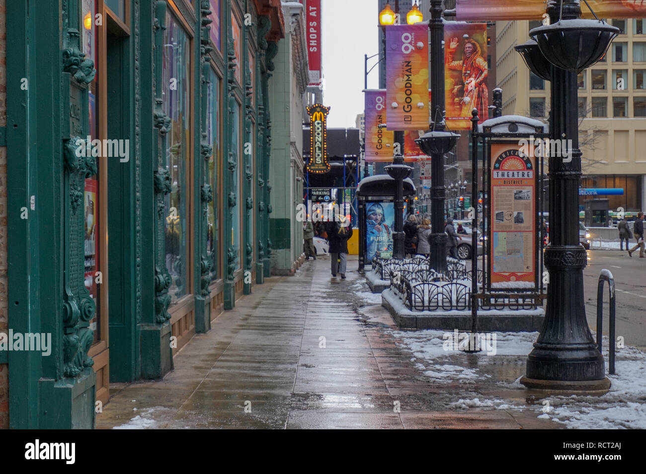 Chicago, IL, USA - 3/23/2015: Colorful Chicago sidewalk with street lamps and banner signs. Taken on a rainy day at dusk. The Windy City. - Stock Image