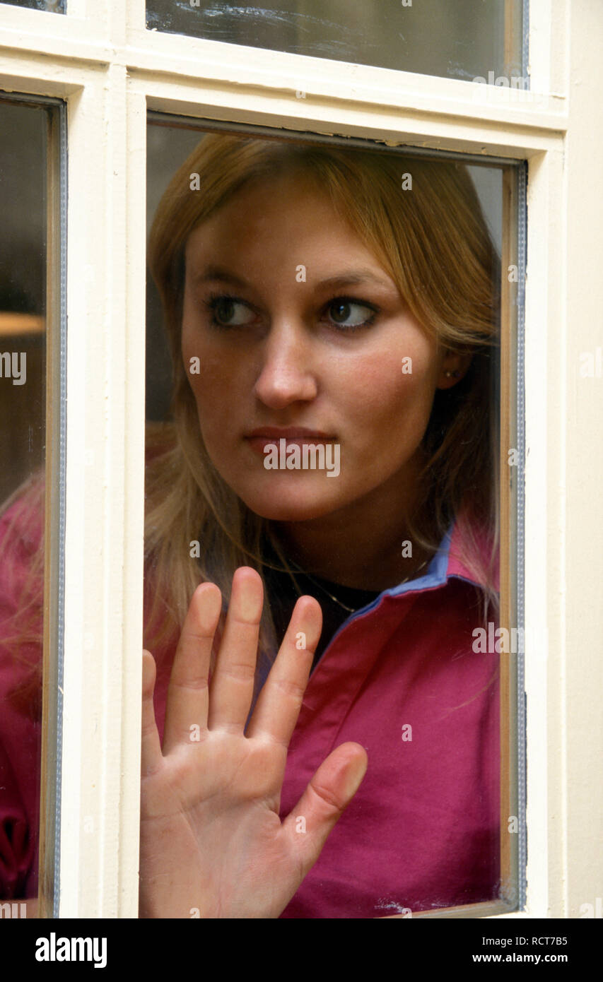 unhappy young woman peering through window - Stock Image