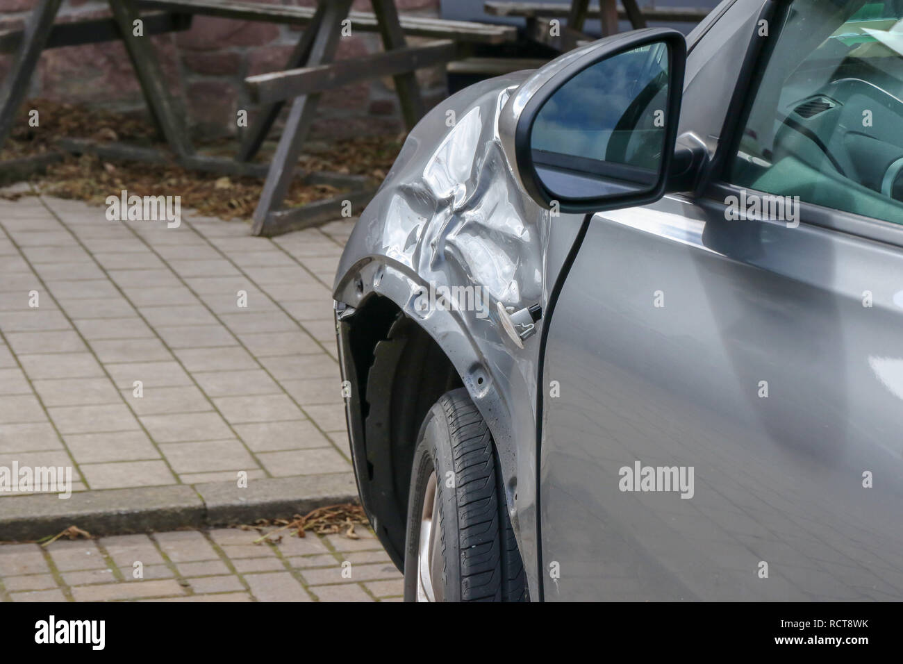 Damaged car - parked grey car with damaged panel on front near-side wing - Stock Image