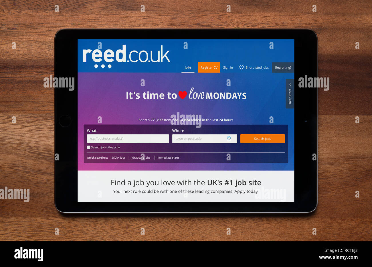 The website of Reed recruitment is seen on an iPad tablet, which is resting on a wooden table (Editorial use only). - Stock Image