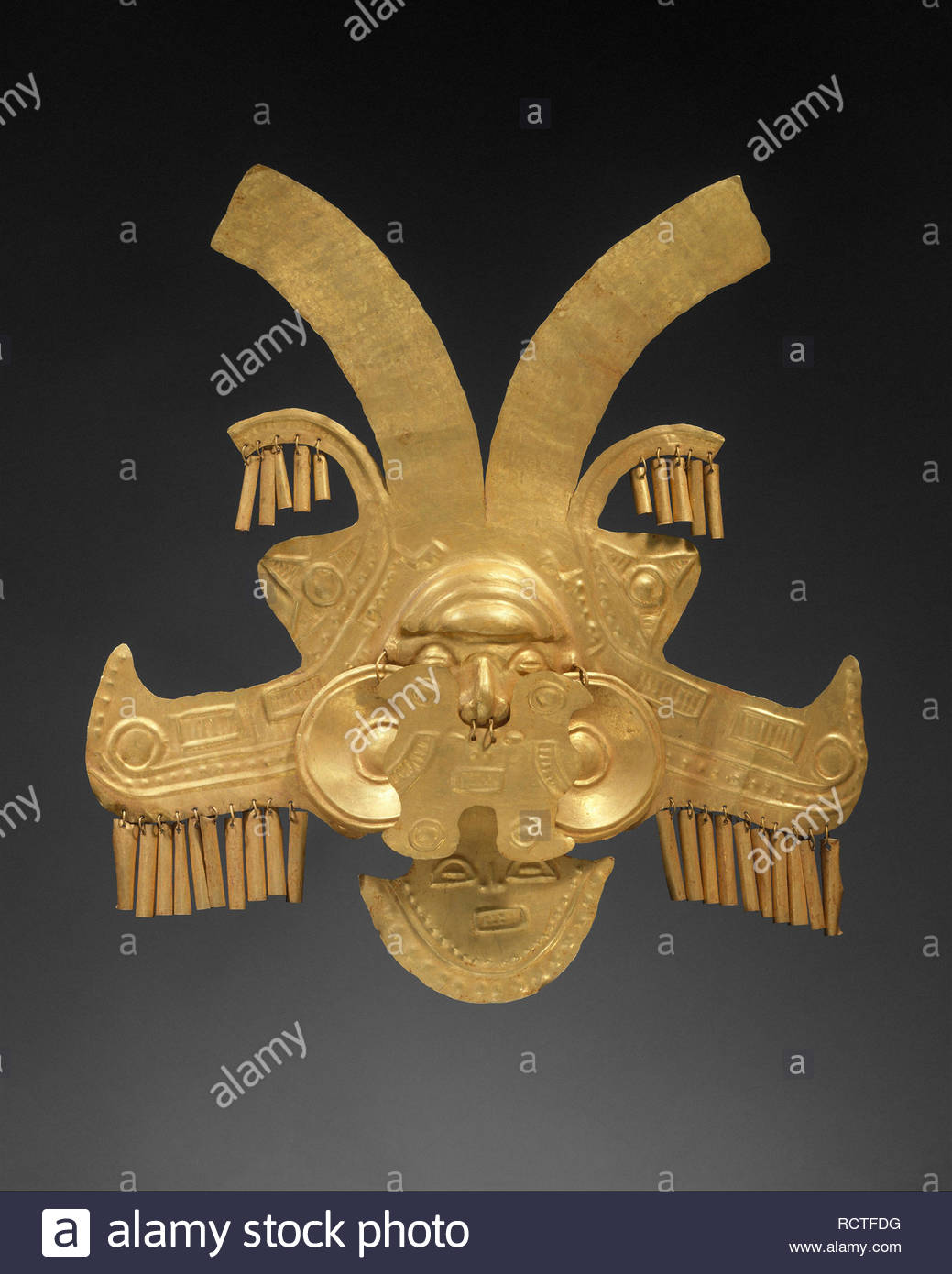 Headdress Ornament, 1st–7th century, Colombia, Calima (Yotoco), Gold, H. 10 x W. 9 3/8 in. (25.4 x 23.8 cm), Metal-Ornaments, Elaborate ornaments like the present example expressed the wealth and status of the wearer. Worn attached to a turban, basketry headdress, or other form of textile construction, it would have offered a spectacular sight when in motion with its many free-swinging surfaces. Stock Photo