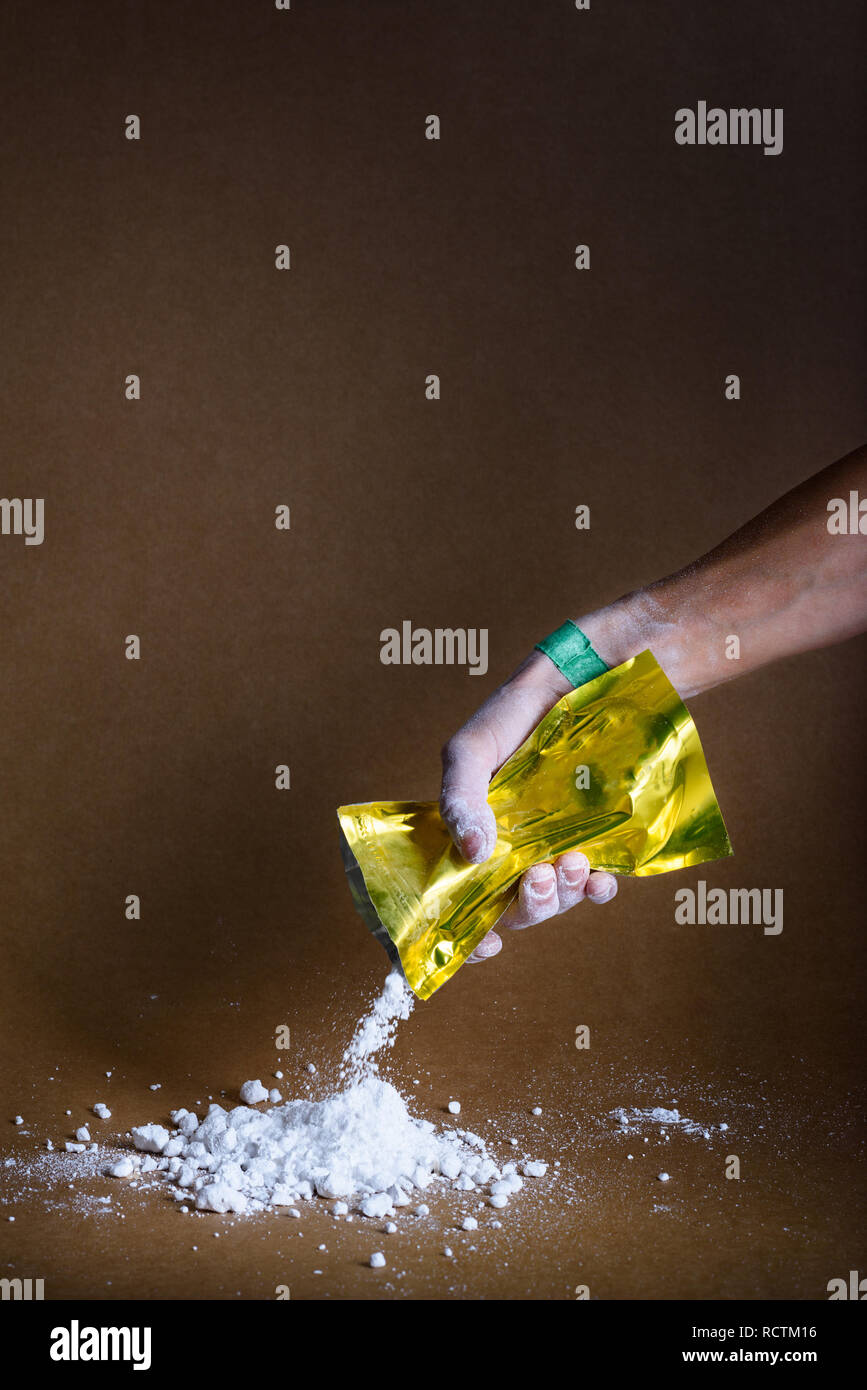 Taped hands of gymnast pouring white chalk powder into a pile. Sport magnesium. - Stock Image