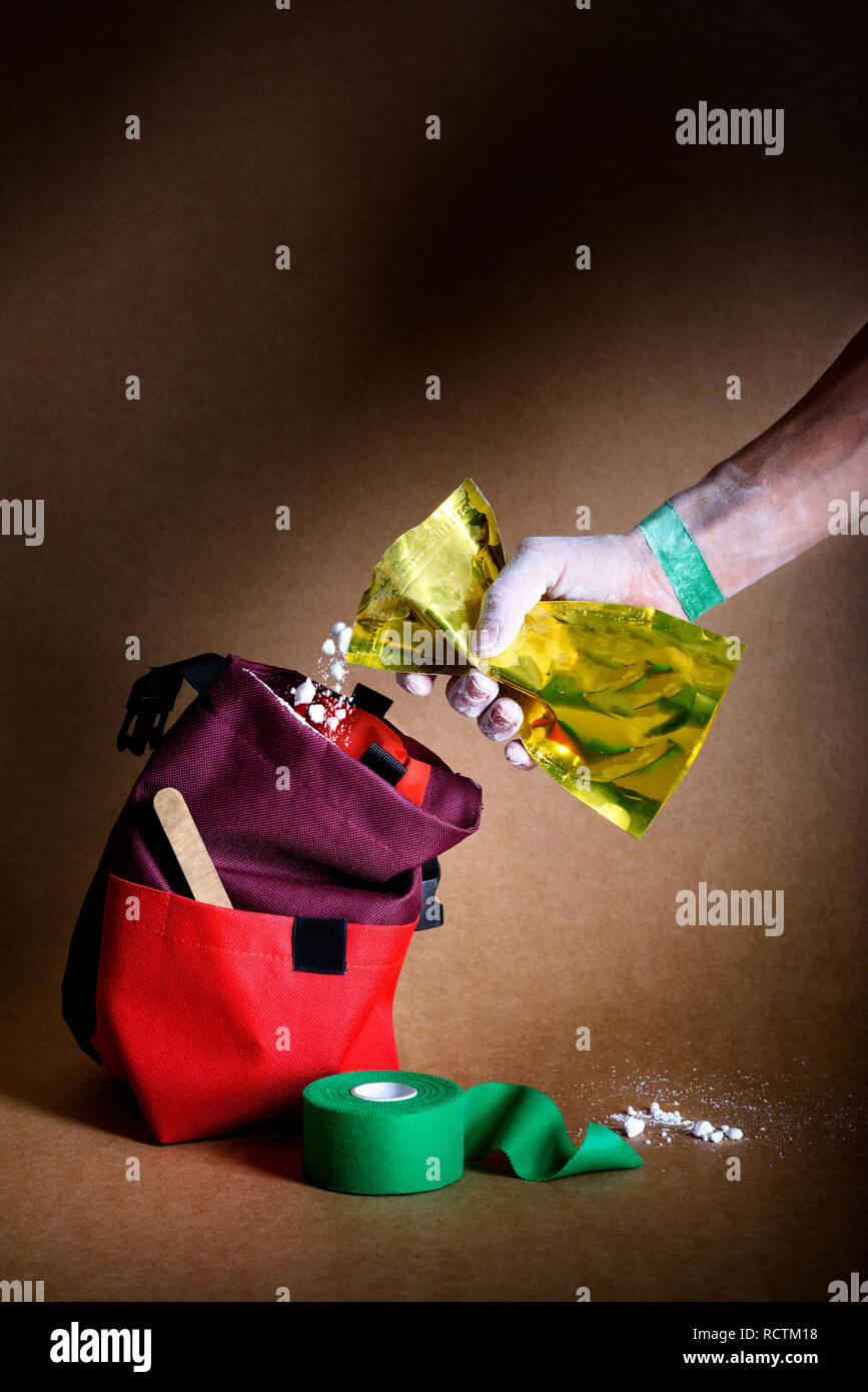 Taped hands of an athlet pouring white chalk powder into a climbing bag. Sport magnesium. - Stock Image
