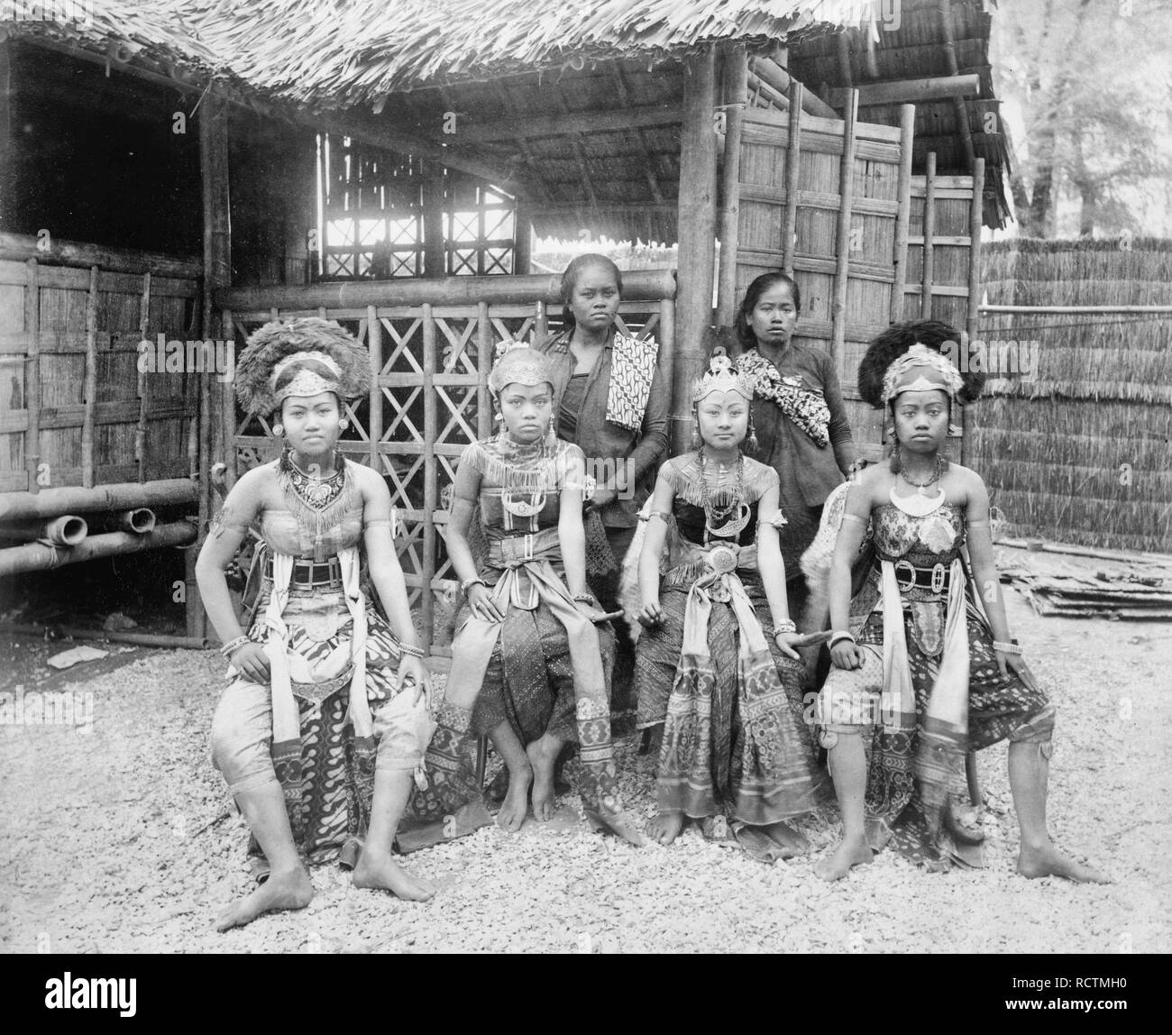Six Javanese women, two in native dress, four in costume, full-length portrait, seated in front of Javanese dwelling, Paris Exposition, 1889 - Stock Image