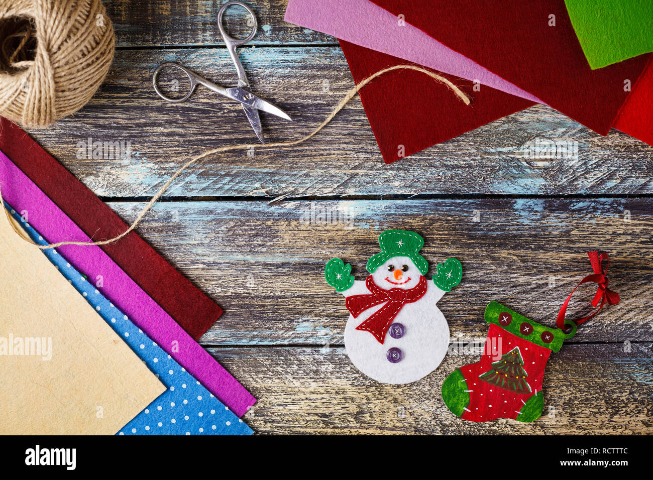 New Year snowman toy from felt at blue wooden background with felt pieces and scissors - Stock Image