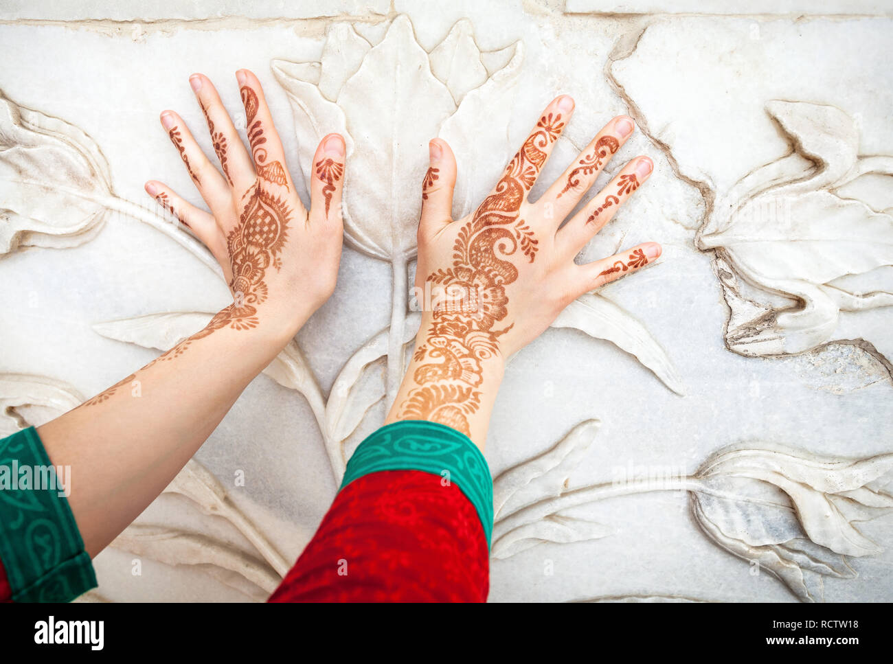 Woman in red Indian costume touching white marble wall with floral pattern by hands in henna painting in Taj Mahal in Agra, Uttar Pradesh, India - Stock Image