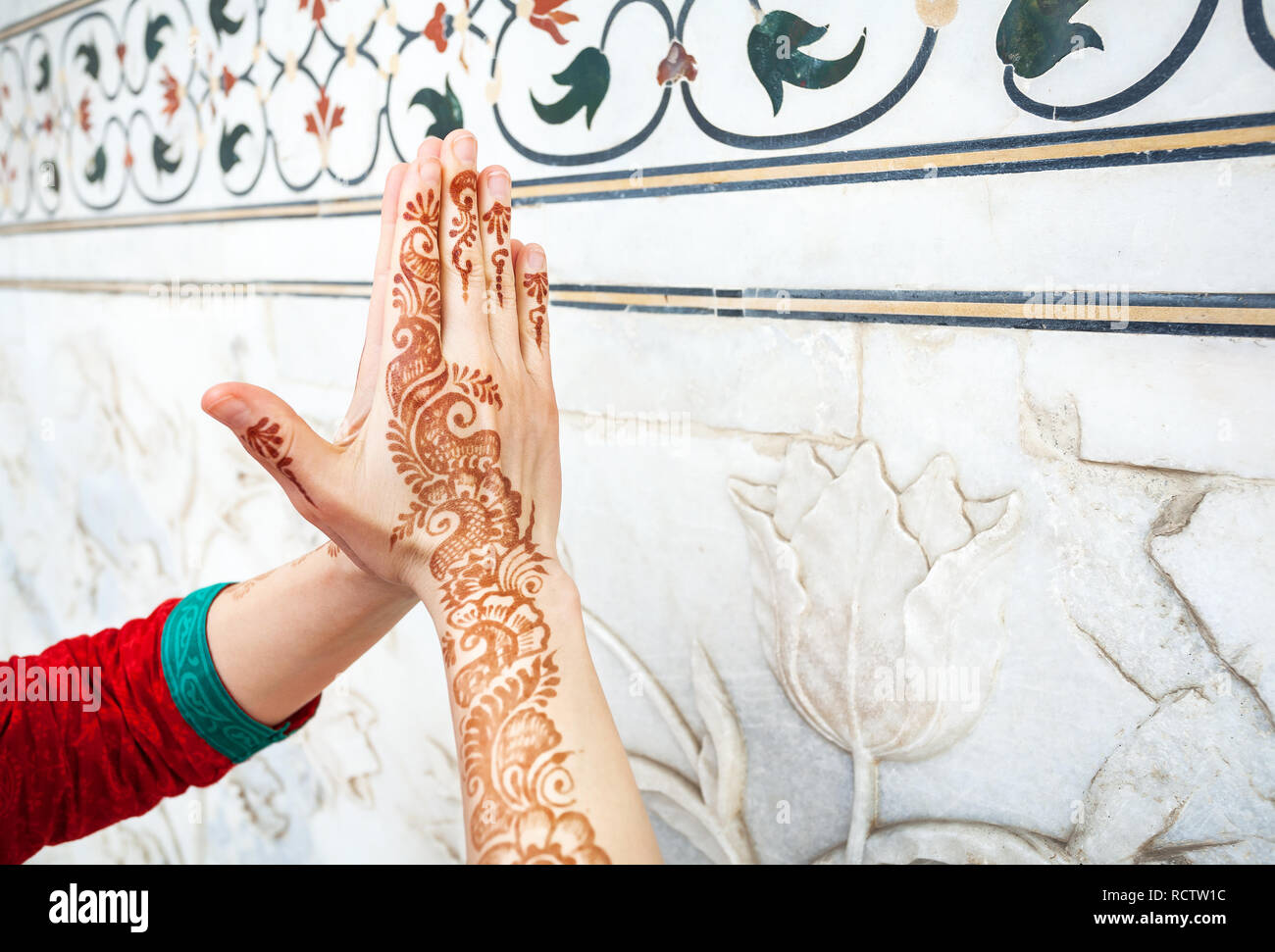 Woman in red Indian costume ding Namaste gesture by hand in henna paintings  near the marble wall with floral pattern in Taj Mahal in Agra, Uttar Prad - Stock Image