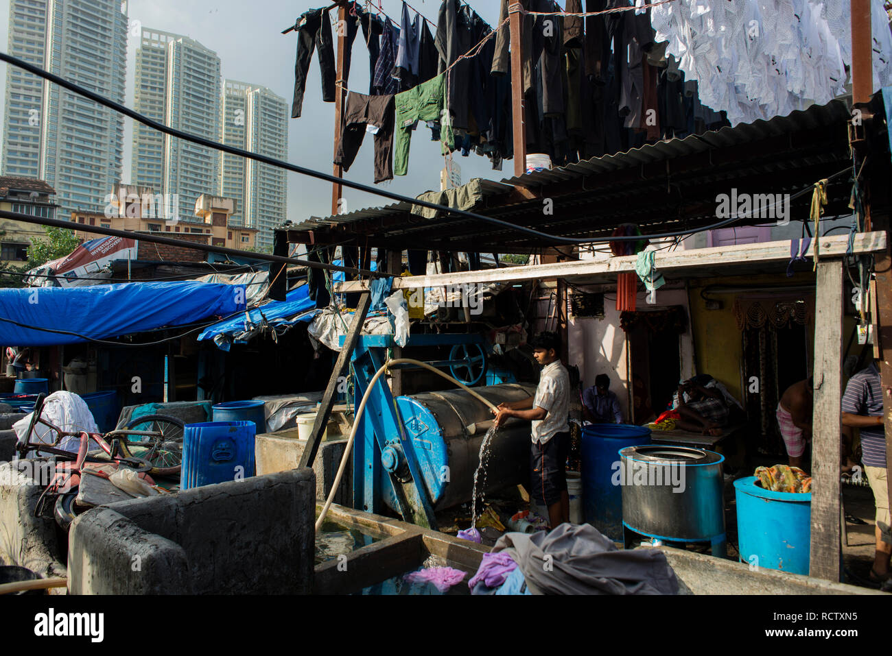Washermen are at work in an open-air laundromat in Mumbai. - Stock Image