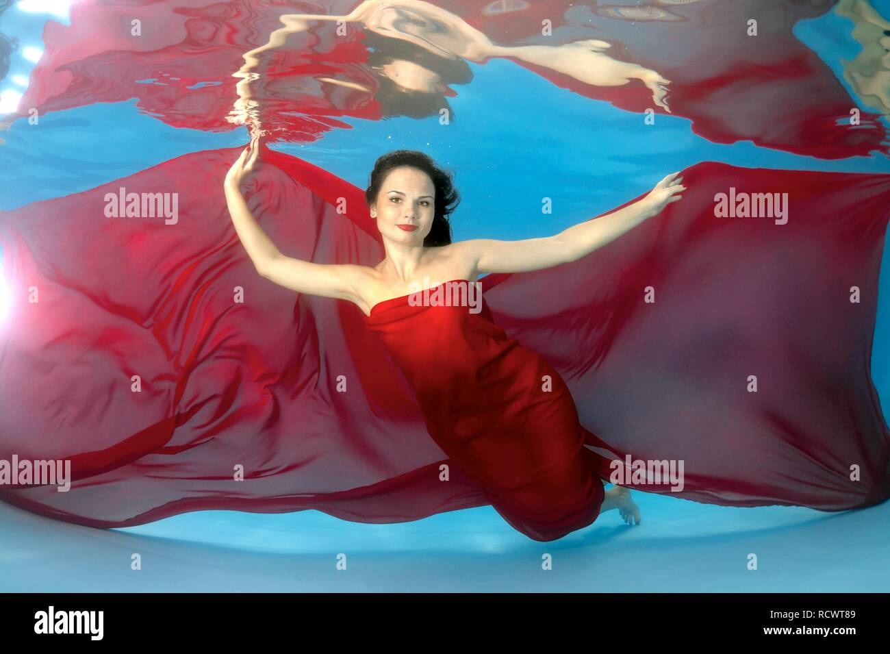 Woman presenting underwater fashion in pool Stock Photo