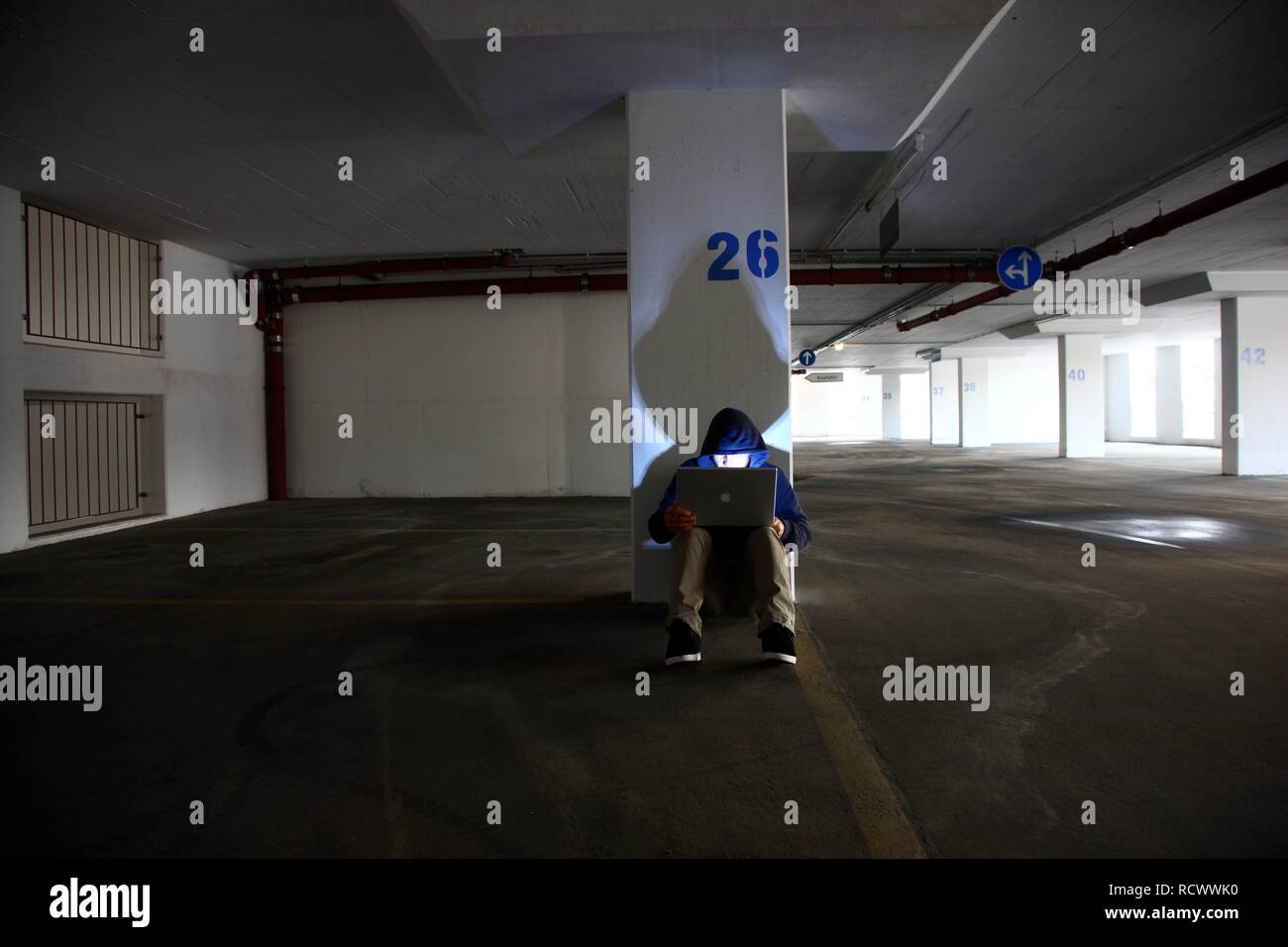 Man surfing on a laptop computer in an empty multi-storey car park, symbolic image for computer hacking, computer crime - Stock Image