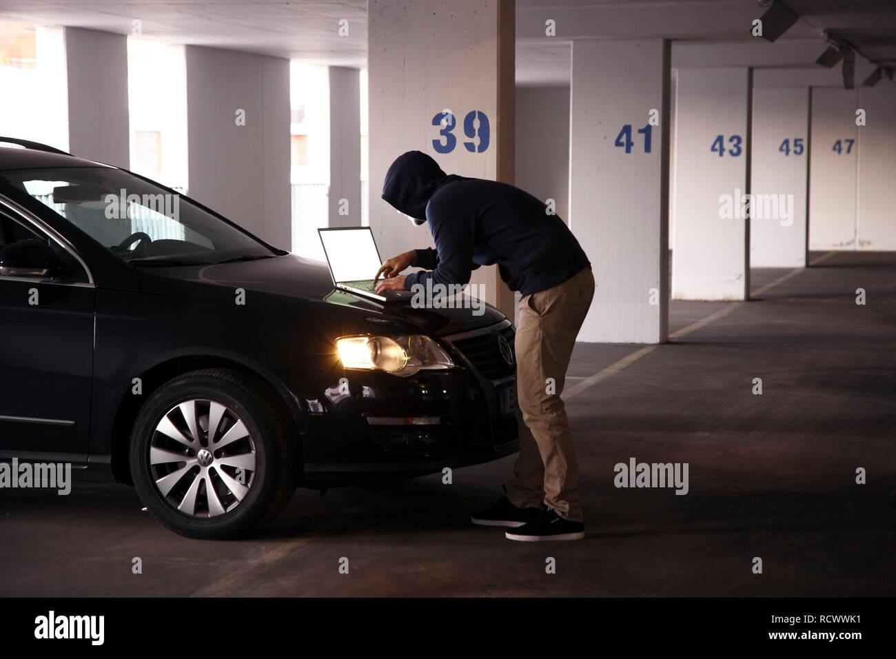 Man surfing on a laptop computer in a multi-storey car park, symbolic image for computer hacking, computer crime, cybercrime - Stock Image