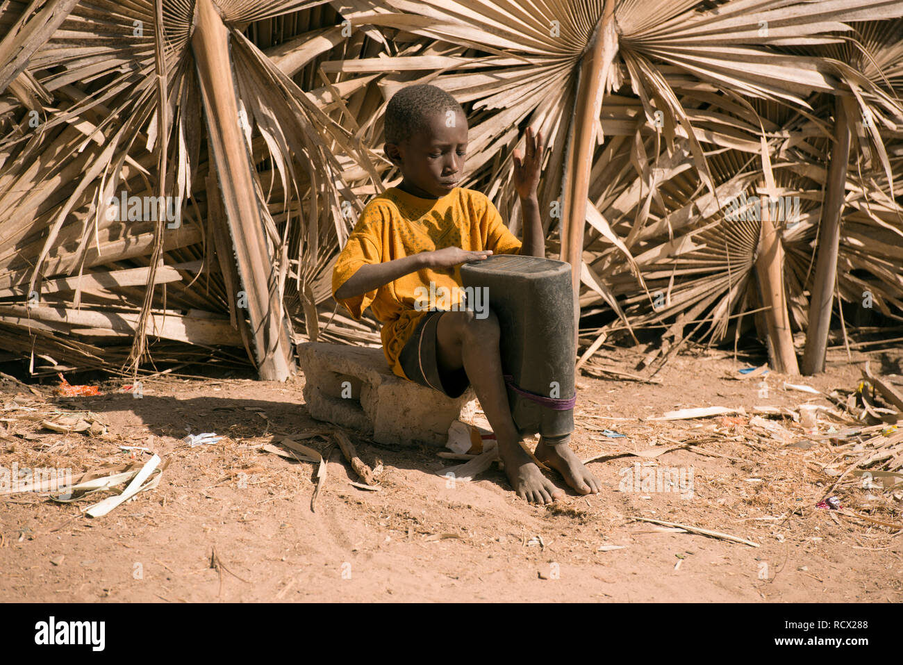 A young indigenous Jola tribe boy plays a drum during a traditional ritual in the village of Berending, The Gambia, West Africa. - Stock Image