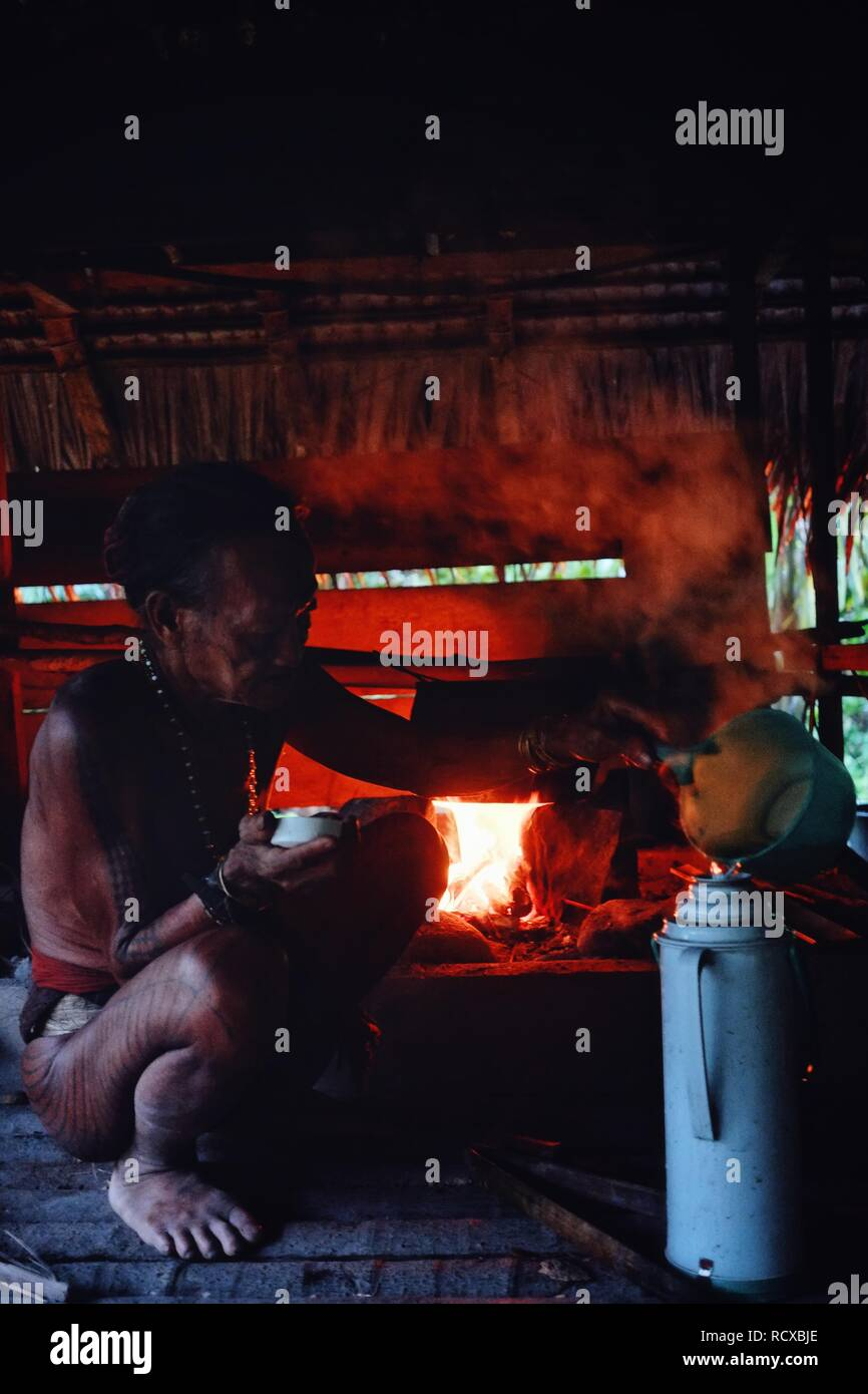 Muara Siberut, Mentawai Islands / Indonesia - Aug 15 2017: Tribal elder Toikot is preparing a tea during the afternoon heat at his jungle home - Stock Image