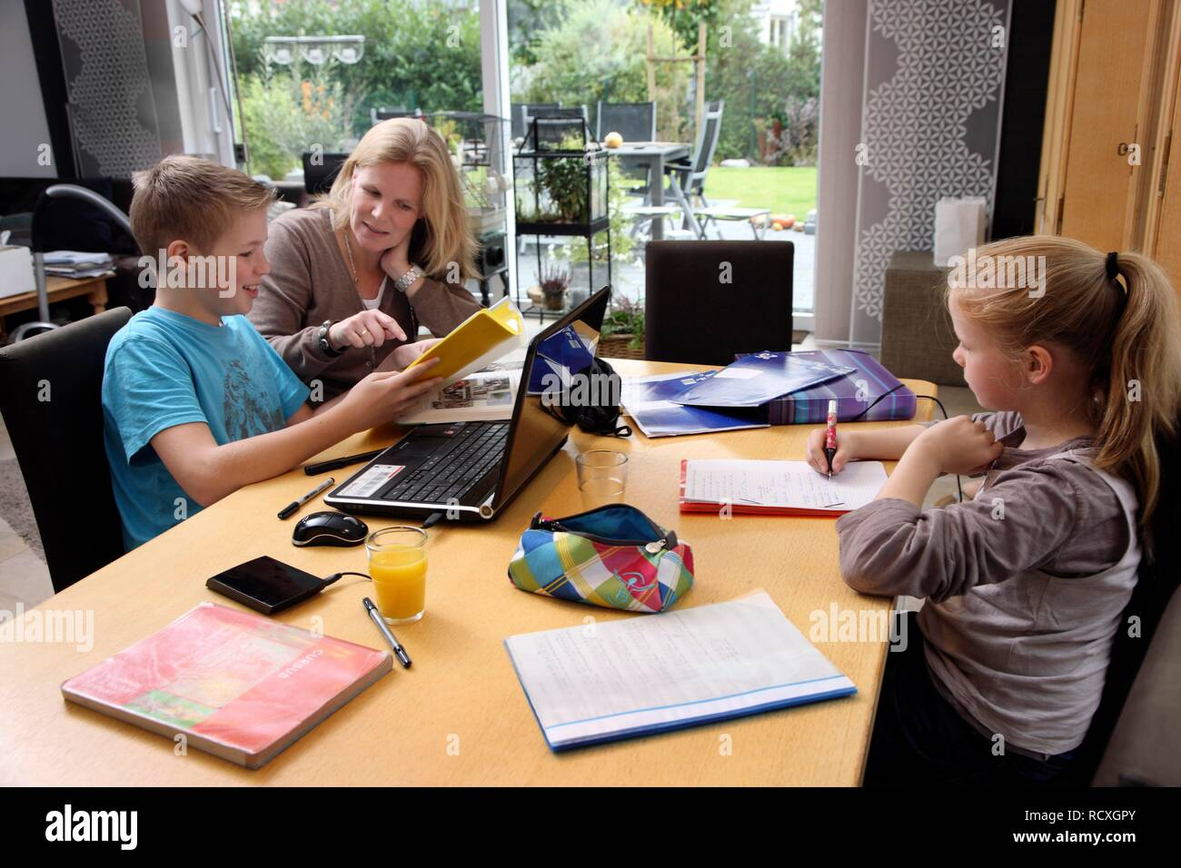 Siblings doing their homework in the living room, their mother is helping them Stock Photo