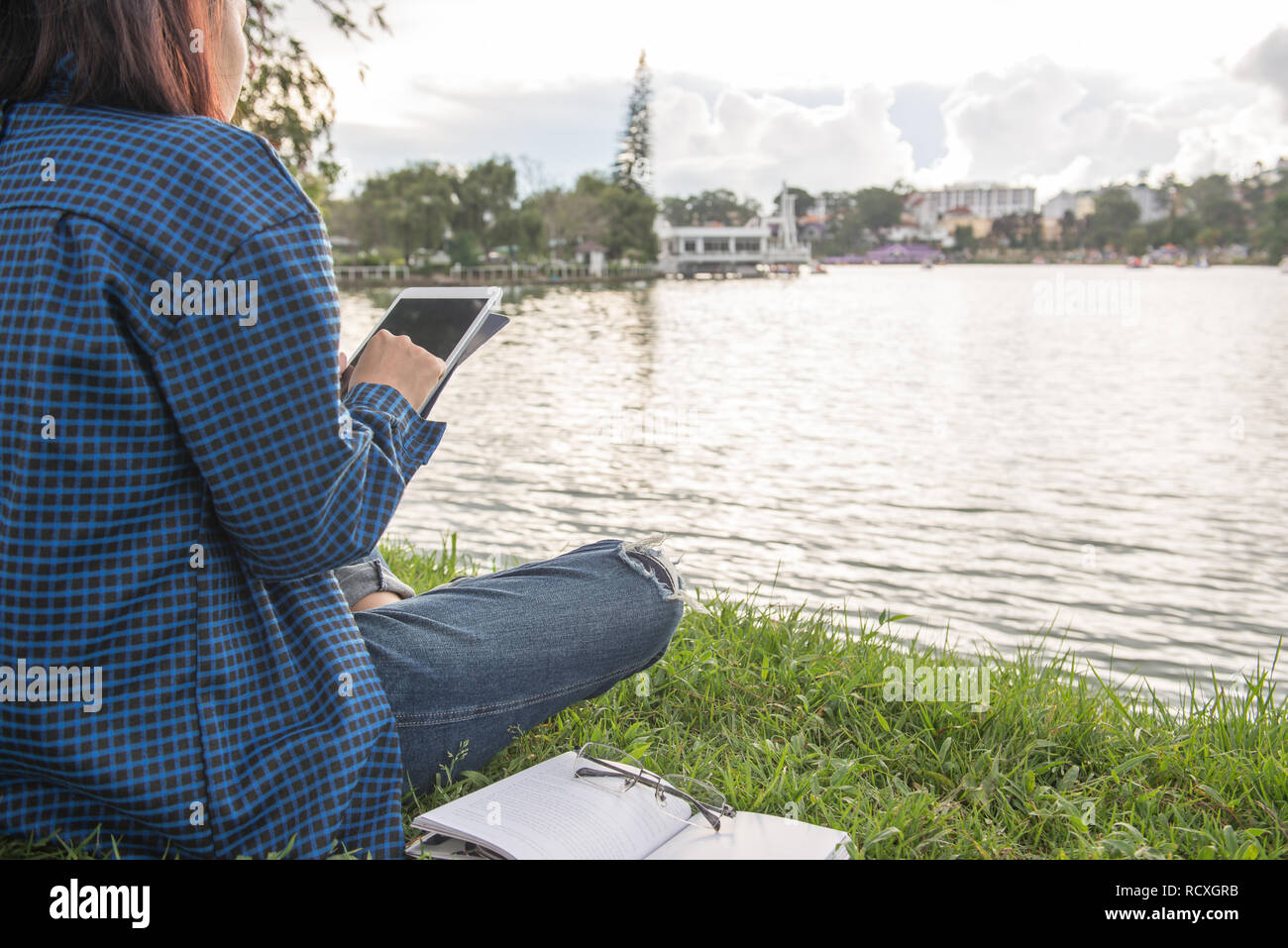 Woman tapping on tablet screen, sitting at a lake - Stock Image