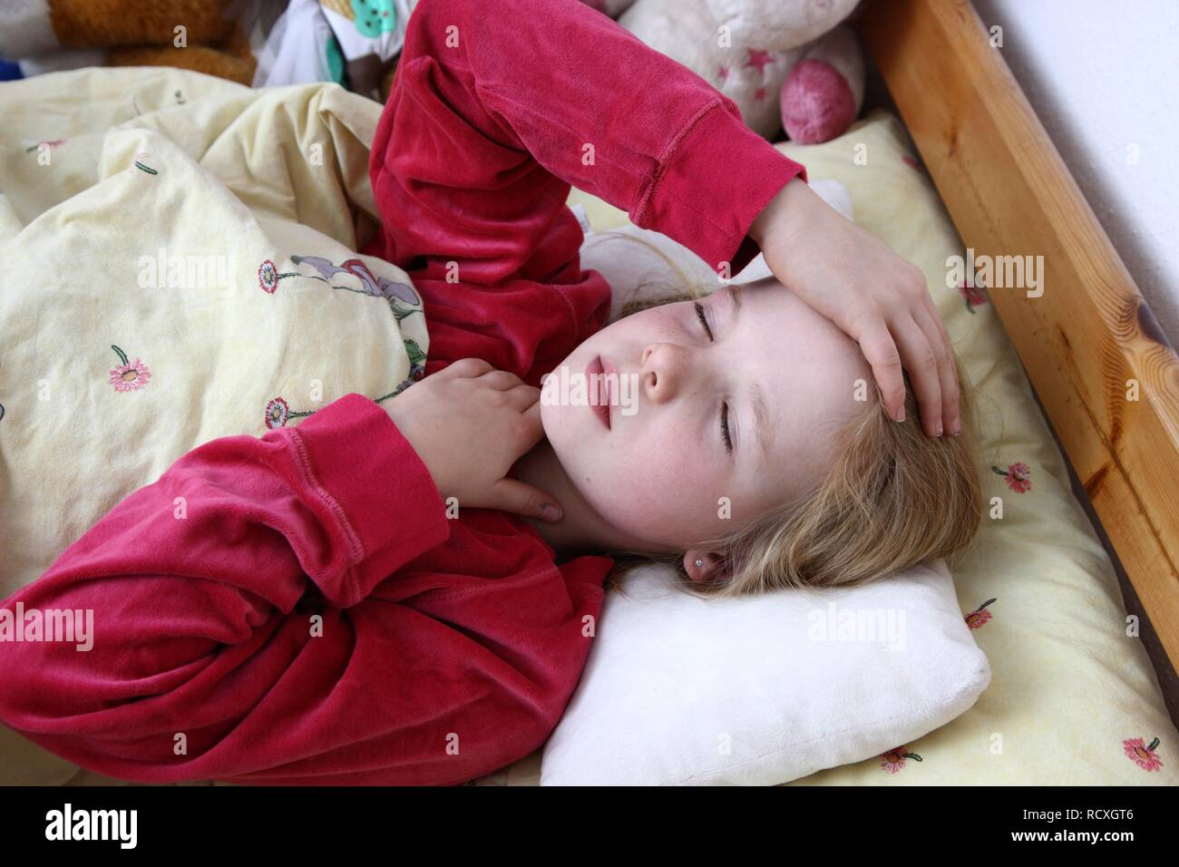 Girl, 10 years old, is ill in bed with a cold, flu, fever - Stock Image