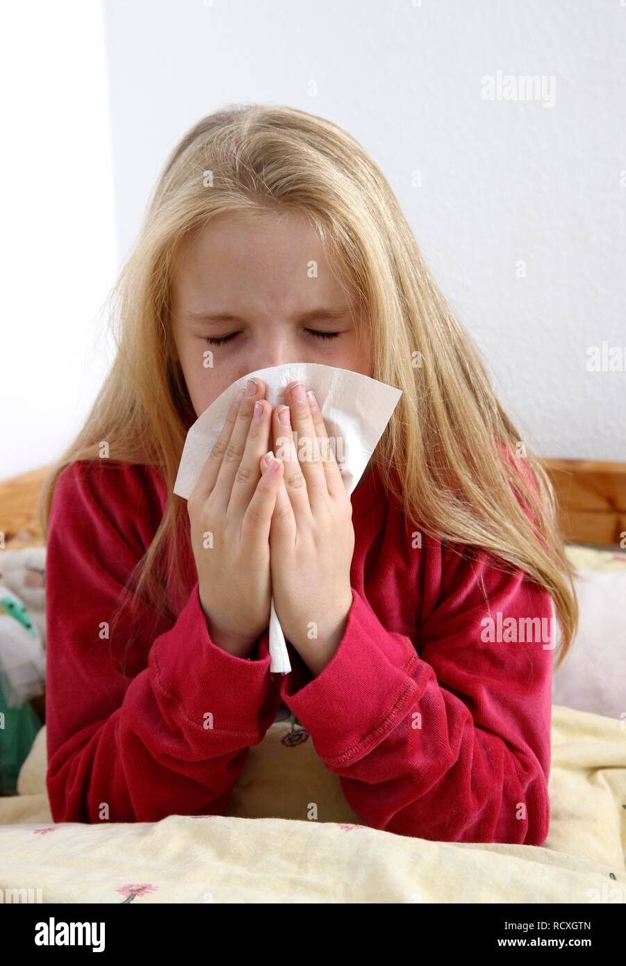 Girl, 10 years old, with a cold, flu, fever, blowing her nose - Stock Image