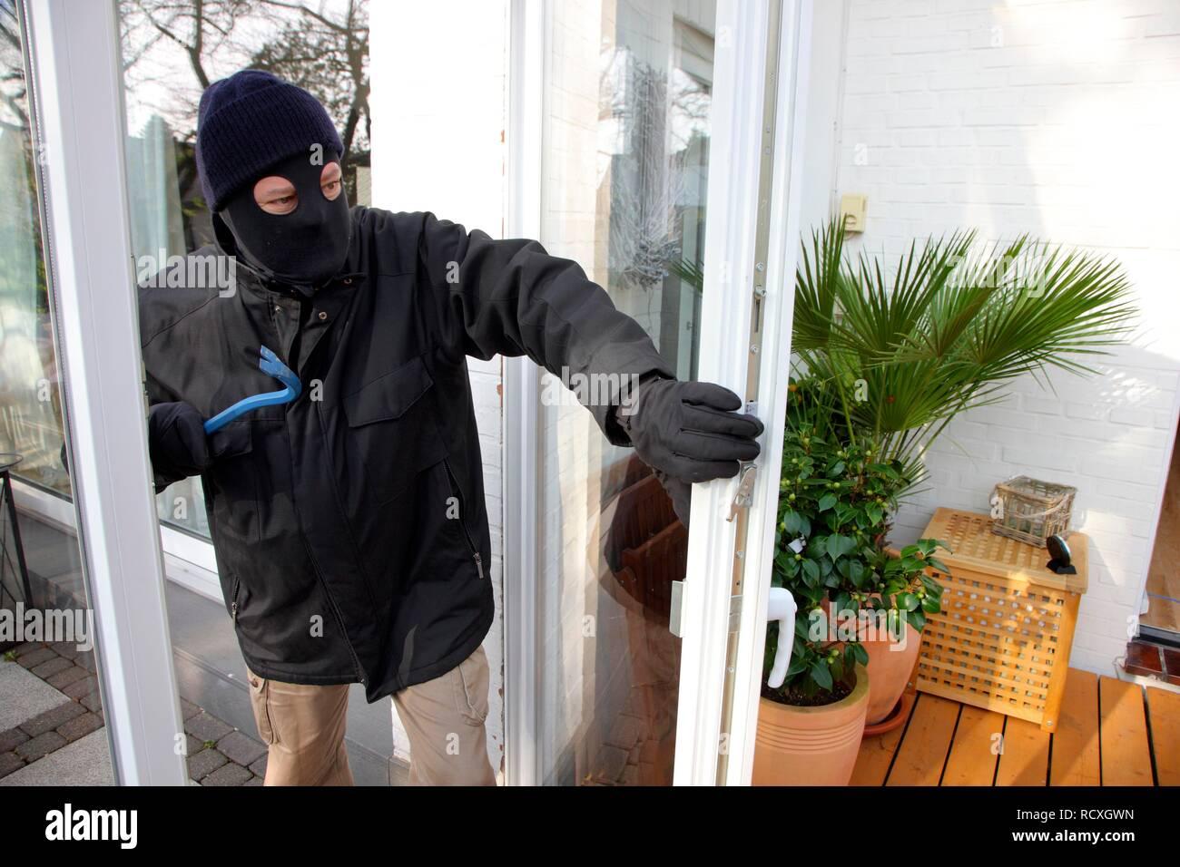 Burglar breaks open the door of the conservatory, symbolic image for domestic burglary - Stock Image