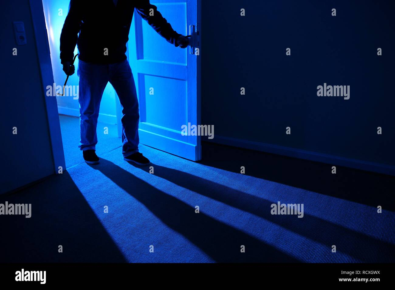 Burglar breaks open the front door and enters the apartment, symbolic image for domestic burglary - Stock Image