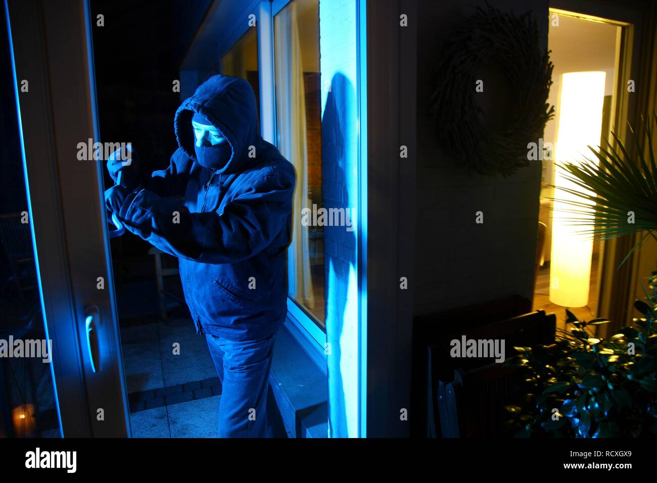 Burglar breaks open the patio door with a crowbar, symbolic image for domestic burglary - Stock Image