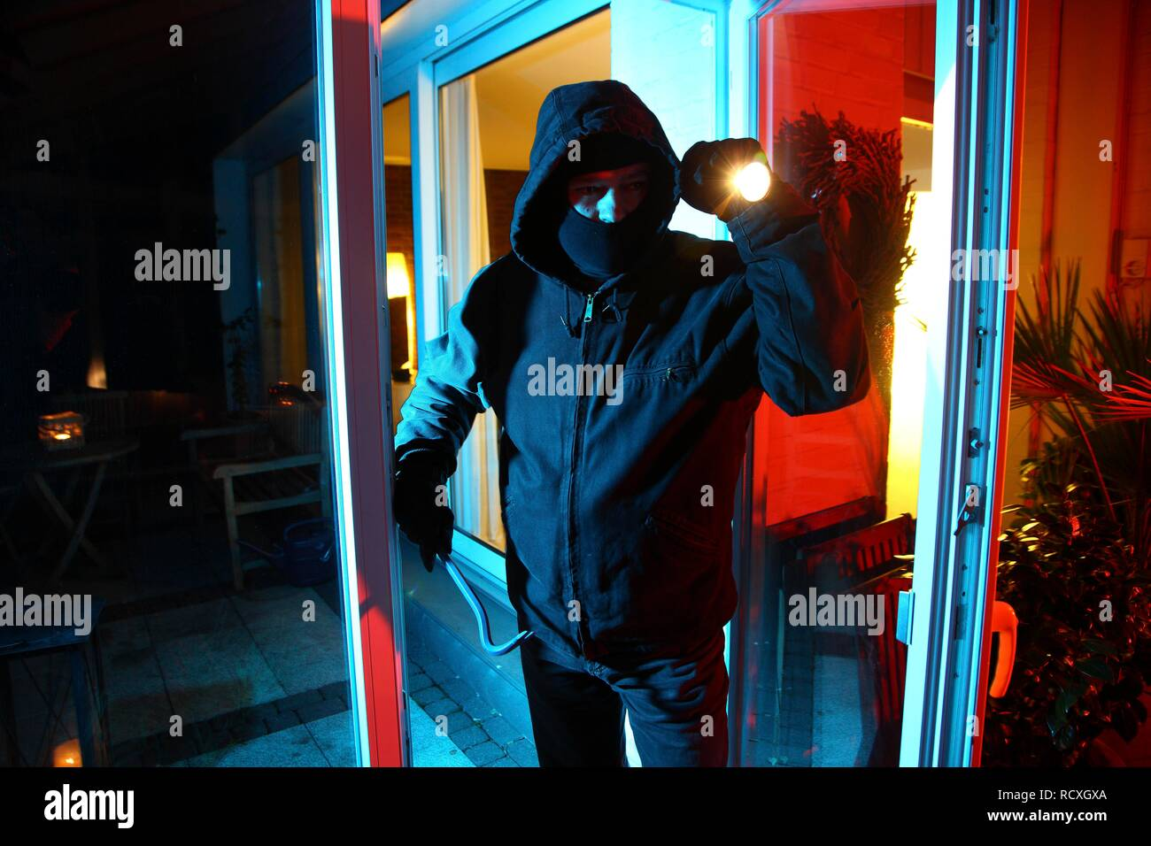 Burglar breaks open the patio door with a crowbar, enters the apartment, symbolic image for domestic burglary - Stock Image