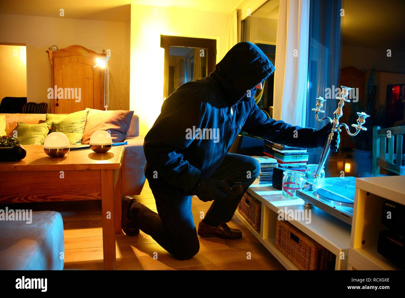 Burglar enters apartment, searches the rooms for valuables, symbolic image for domestic burglary - Stock Image