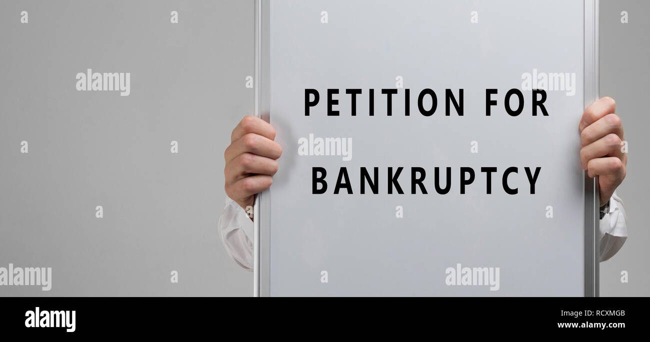 men's hands holding a poster with the inscription petition for bankruptcy isolated on light background - Stock Image