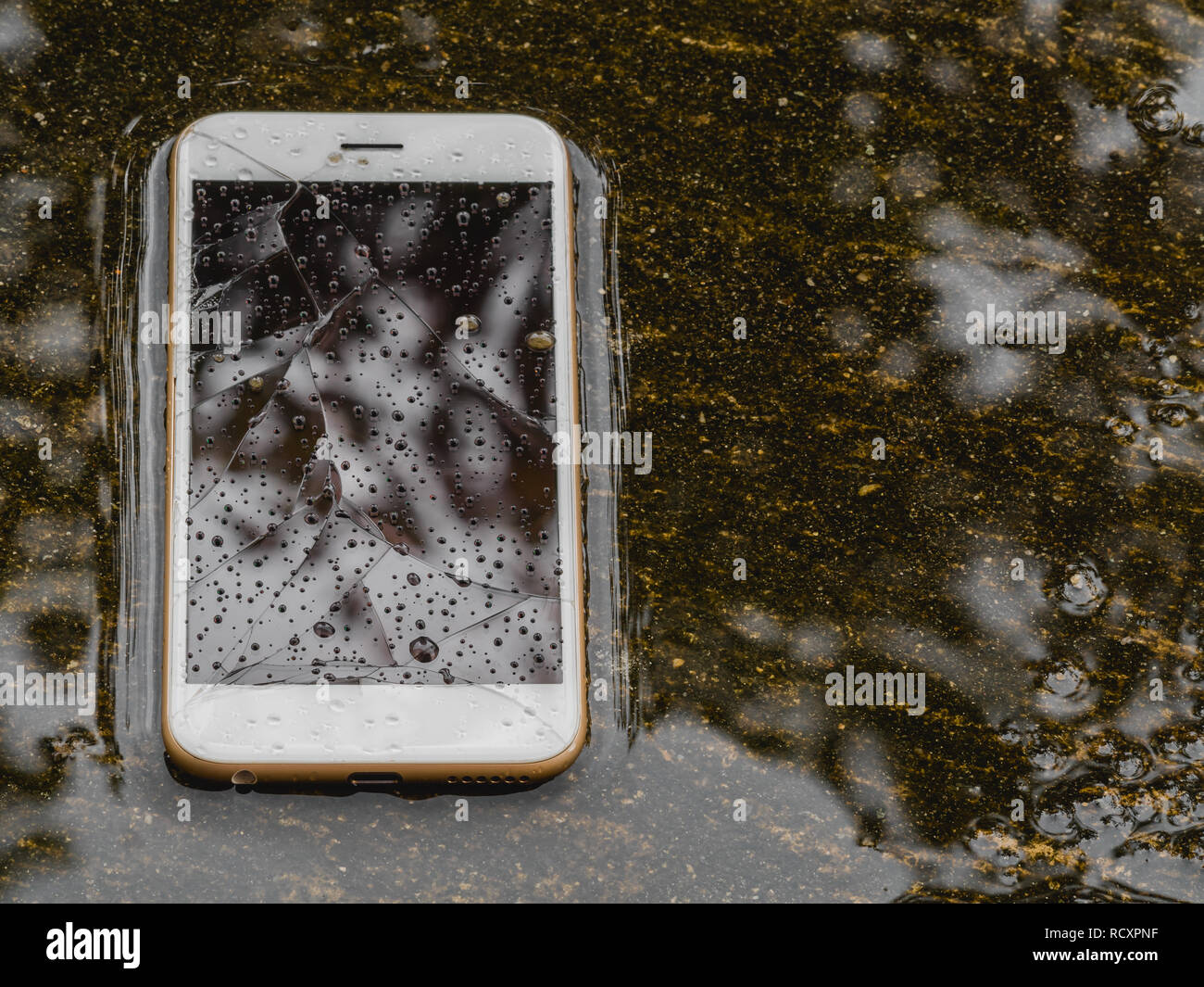 Cracked screen and wet smart phone dropped on flooding floor