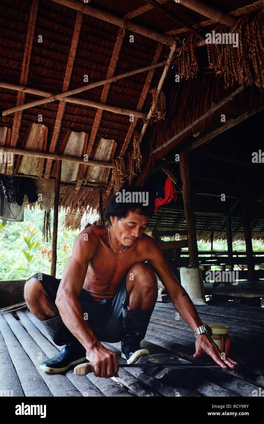 Muara Siberut, Mentawai Islands / Indonesia - Aug 15 2017: Tribal member Aman sharpening his machete at his jungle home - Stock Image