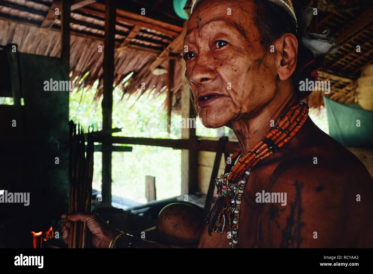 Muara Siberut, Mentawai Islands / Indonesia - Aug 15 2017: Tribal elder Toikot drying poisoned arrows over the fire at his rainforest home - Stock Image