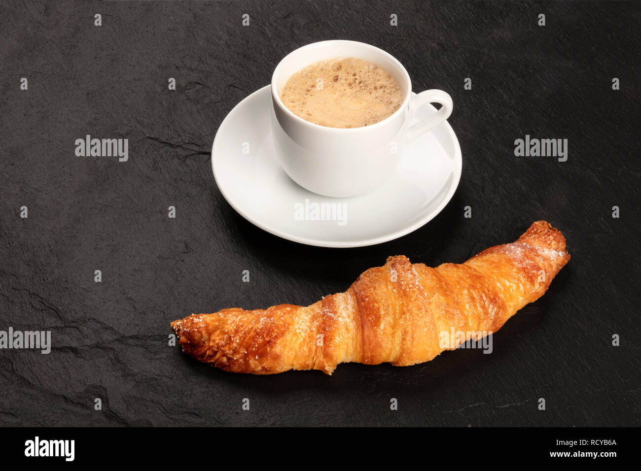 A photo of a croissant with a cup of coffee on a black background with copy space - Stock Image