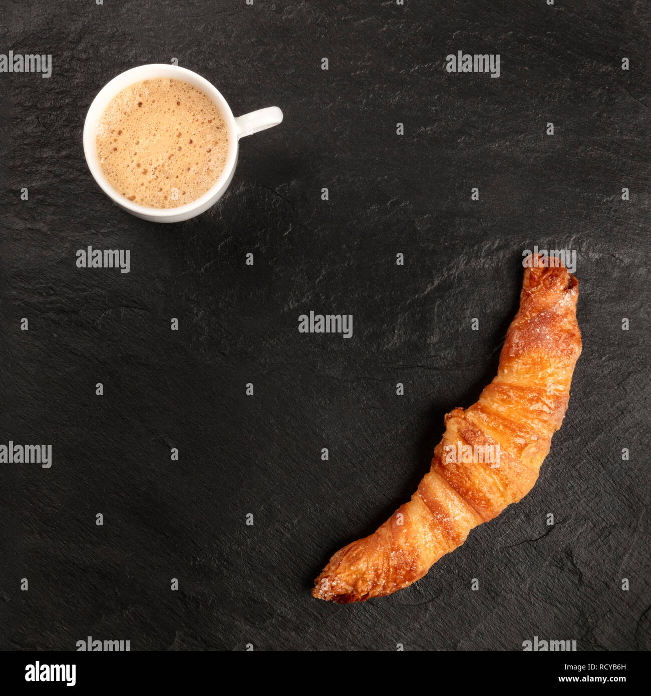 A photo of a croissant with a cup of coffee, shot from the top on a black background, forming a frame for copy space - Stock Image