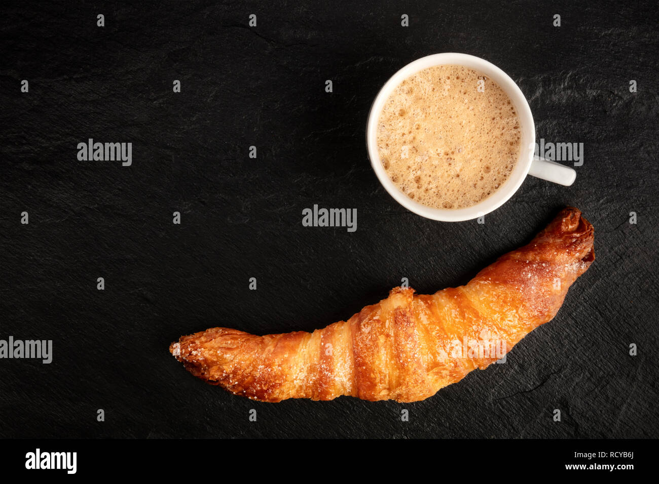 A photo of a croissant with a cup of coffee, shot from the top on a black background with a place for text - Stock Image