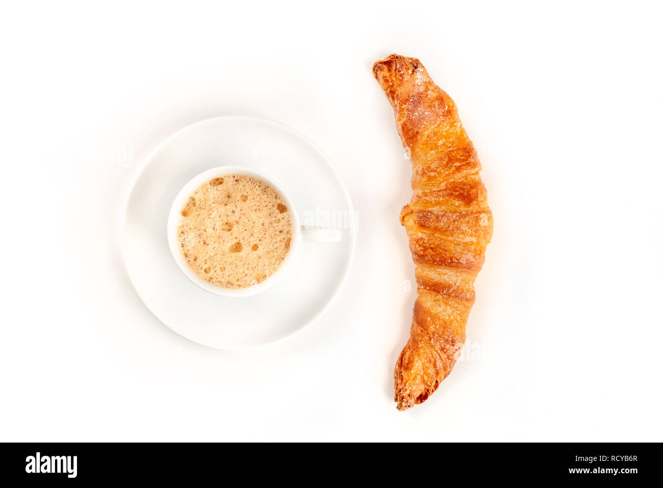 An overhead photo of a cup of coffee with a croissant, shot from above on a white background with a place for text - Stock Image