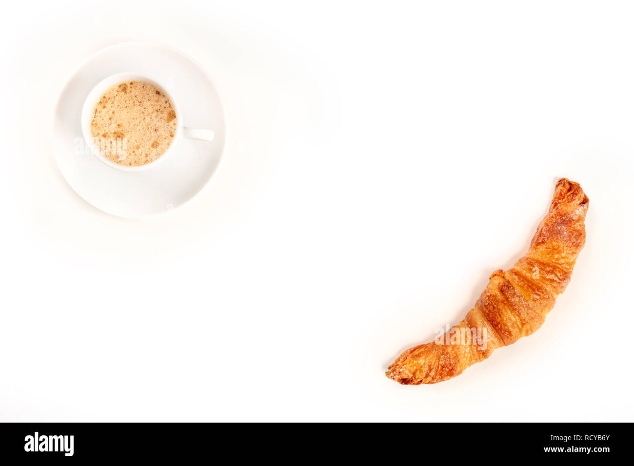 An overhead photo of a cup of coffee with a croissant, shot from above on a white background, forming a frame for copy space - Stock Image