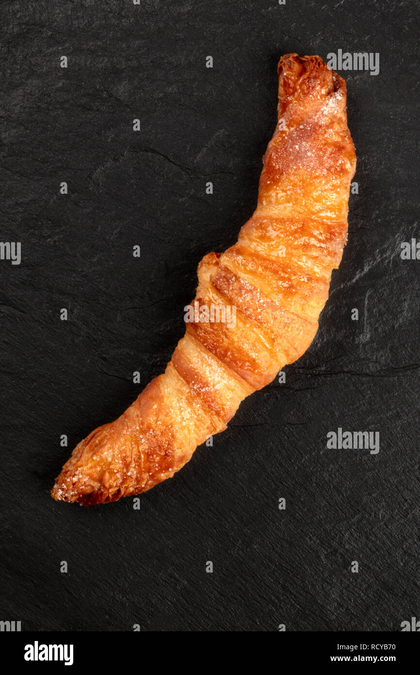 A photo of a croissant on a black background, shot from the top with a place for text - Stock Image
