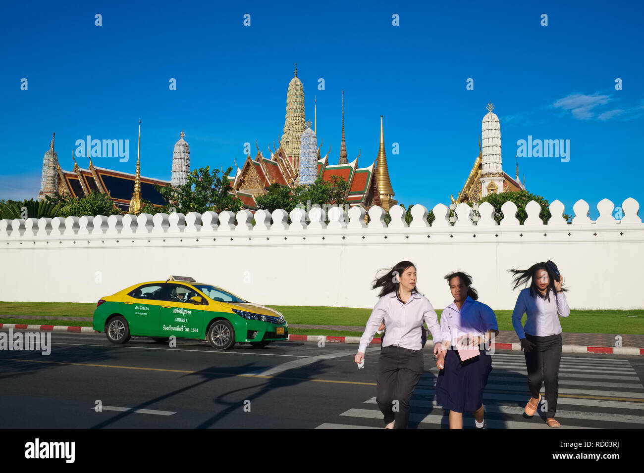 Women rushing over a zebra crossing in front oft the eastern wall of Wat Phra Kaew & Grand Palace, Bangkok, Thailand, as a taxi passes behind them - Stock Image