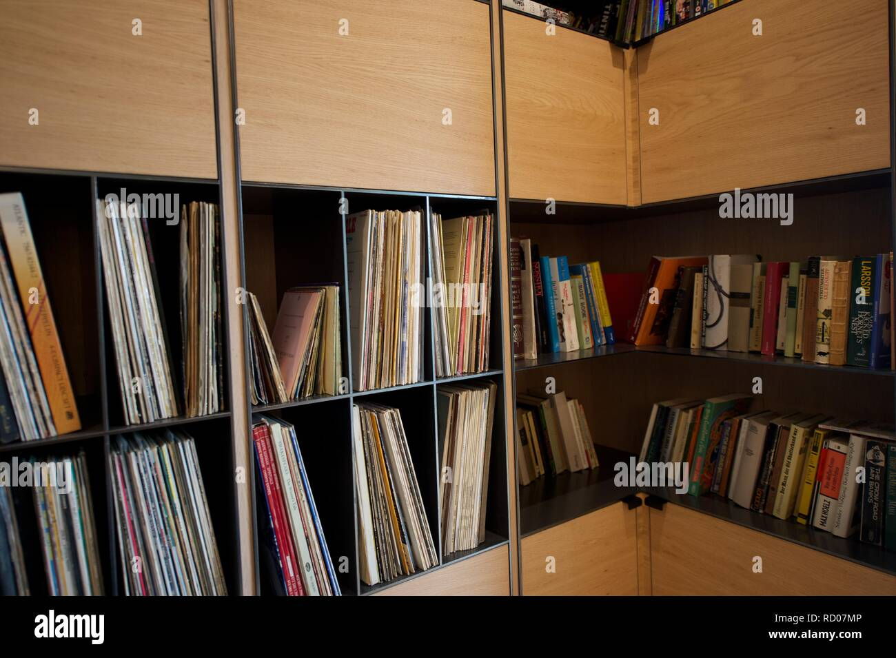 Books And Various Media On Home Library Shelves Stock Photo