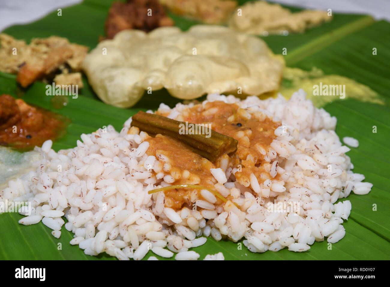 Traditional Onam Sadhya boiled rice served with curries, dessert payasam on banana leaf a grand feast on Onam, Vishu harvest festival of Kerala India - Stock Image