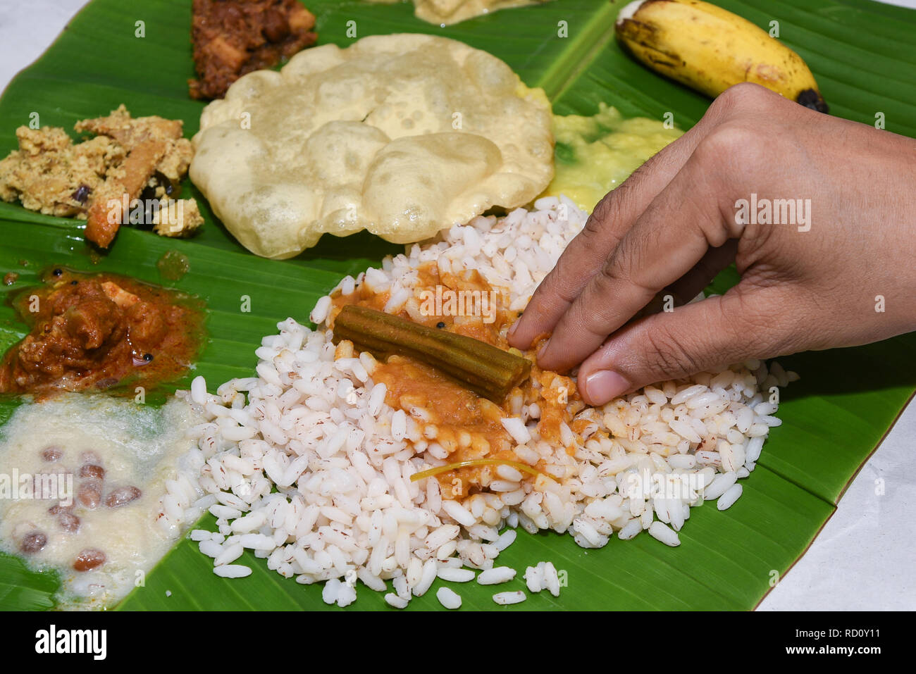 Traditional Onam Sadhya boiled rice with curries, payasam eating on banana leaf with hand. Grand feast on Onam, Vishu harvest festival of Kerala India - Stock Image