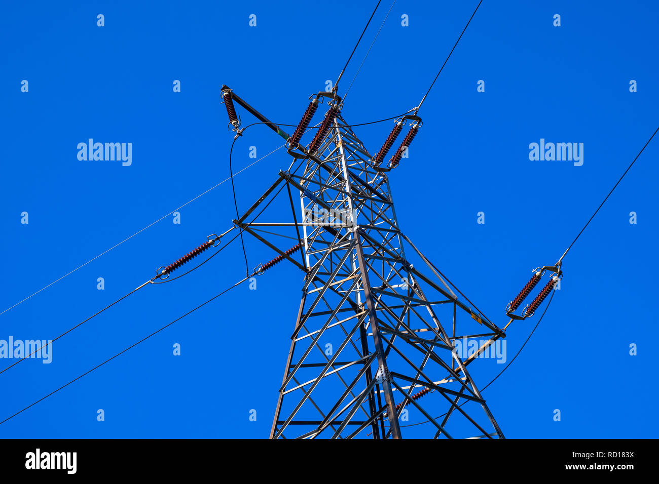 High voltage transmission line supported by the metal construction of a high-voltage electric pole with power insulators and connectors on a deep blue - Stock Image