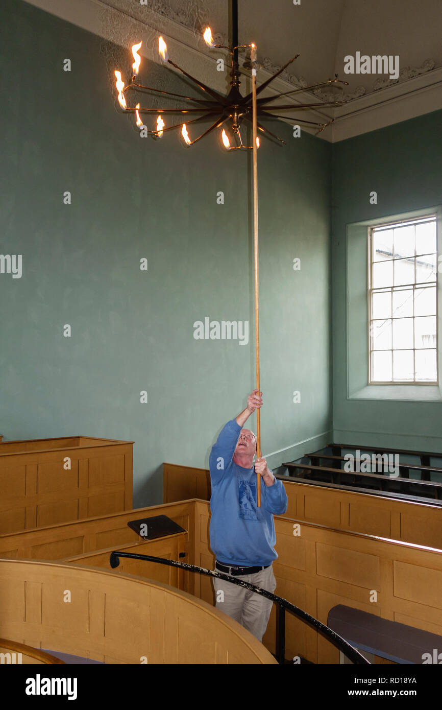 The Judge's Lodging, Presteigne, Powys, UK. An award winning museum of Victorian life. Lighting the 1860 gasolier in the original courtroom of 1830 - Stock Image