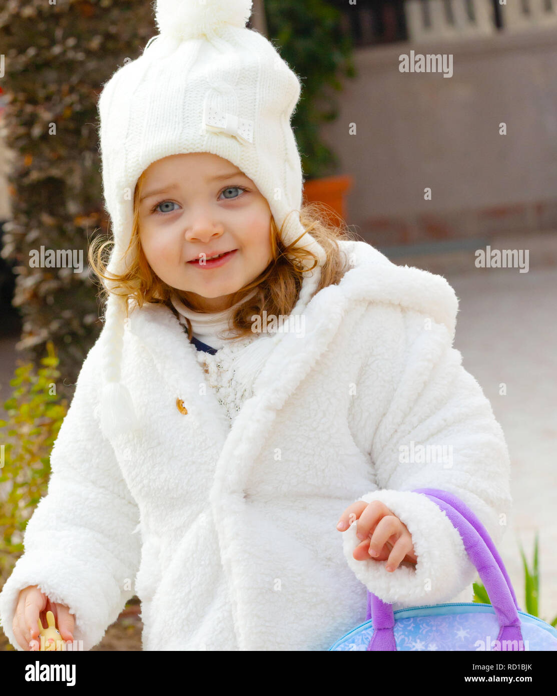 Pretty girl with wool hat and and white coat in a garden at winter. - df3b7befa684
