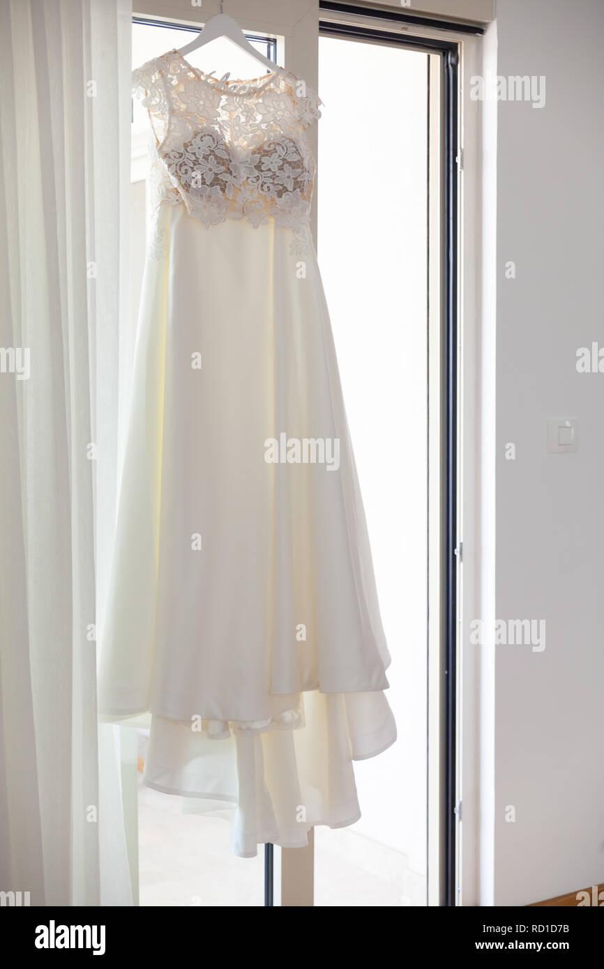 wedding dress hanging on a hanger - Stock Image