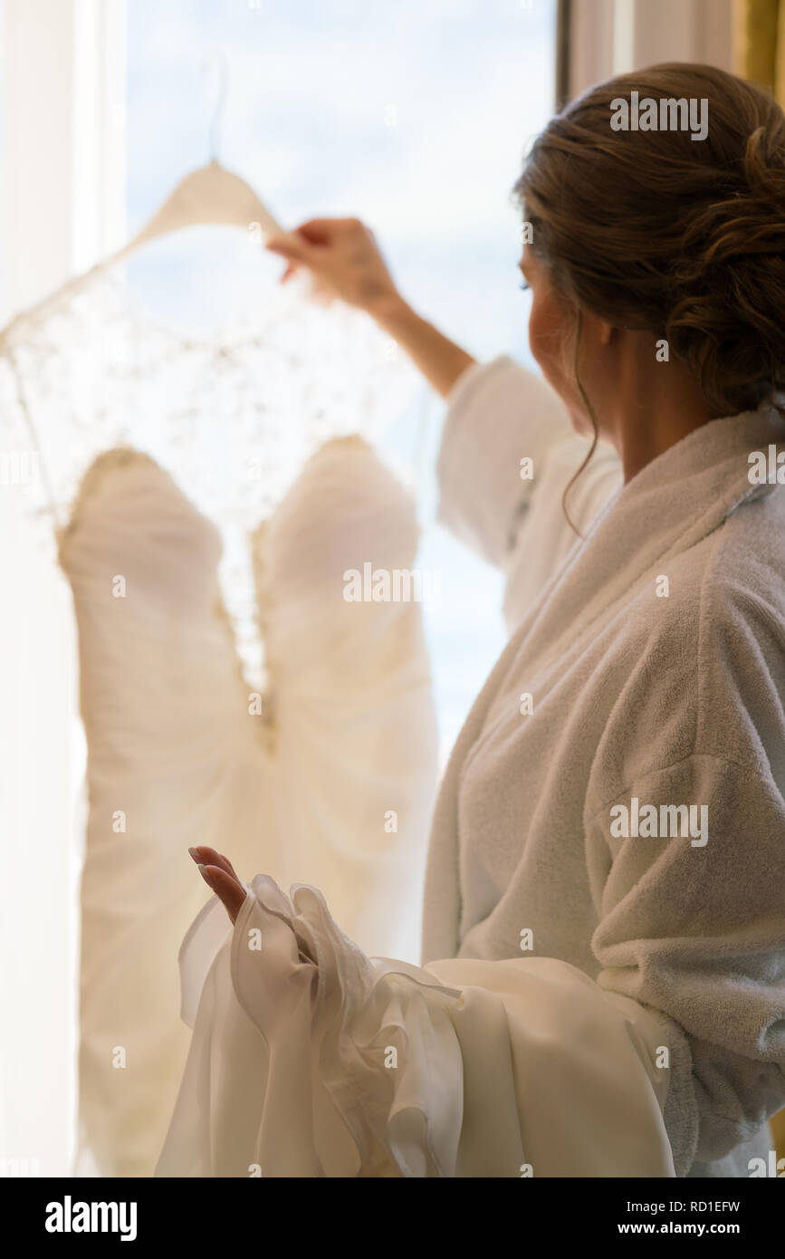 wedding dress in the hands of the bride - Stock Image