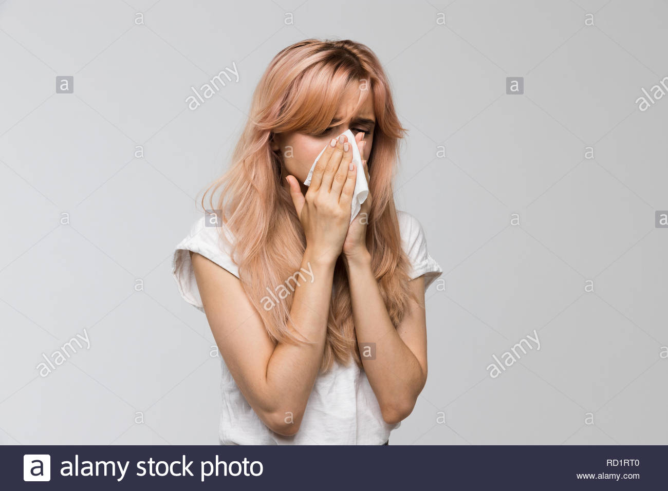 Portrait of young beautiful woman blowing her nose into a paper napkin, closed eyes/sneezing, allergy symptoms, flu, rhinitis, cold, sickness. - Stock Image