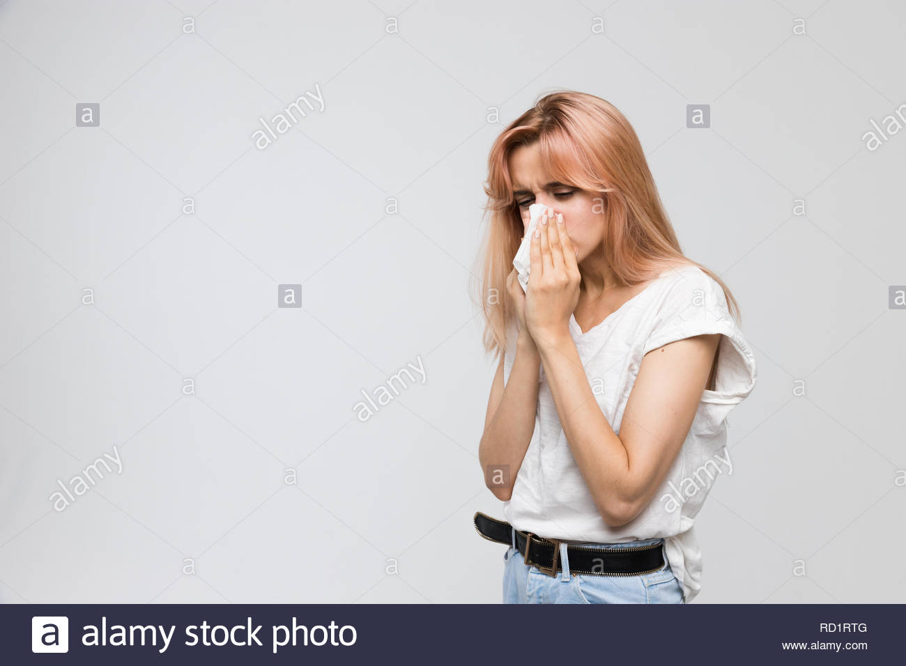 Studio portrait of young beautiful woman blowing her nose into a paper napkin/cold, sneezing, allergy symptoms, flu, rhinitis, sickness. - Stock Image
